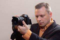 Den unga manliga videopd kameraman, fotograf, skjuter videoen eller tar ett foto p? kameran arkivfoto