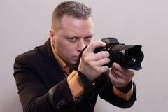 Den unga manliga videopd kameraman, fotograf, skjuter videoen eller tar ett foto p? kameran arkivfoton