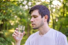 Den unga mannen är dricksvatten från exponeringsglas i natur arkivbilder