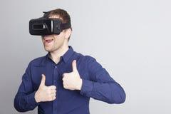 Den unga mannen är glad av vad han ser i virtuell verklighetexponeringsglasen Arkivbilder