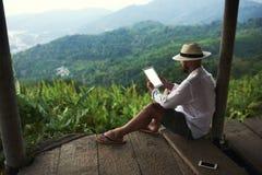 Den unga mannen är läs- finansiell nyheterna på den digitala minnestavlan under hans tur i Thailand arkivfoto