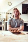 Den unga mannen är olycklig med hans brända pizza för lunch Royaltyfri Foto