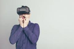 Den unga mannen är rädd av vad han ser i virtuell verklighetexponeringsglasen Royaltyfri Bild