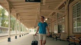 Den unga mannen är resa och gå på plattformen för järnvägstationen med resväskan arkivfilmer