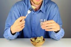 Den unga mannen äter klimpar med kött med vodka Royaltyfri Fotografi