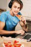 Den unga mannen äter pizza genom att använda bärbara datorn som surfar internet Arkivfoto