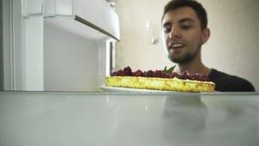Den unga mannen öppnar kylen och tar ut kakan som dekoreras med hallon arkivfilmer