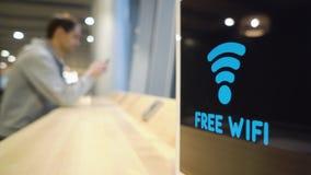 Den unga mannen använder en telefon på en bakgrund av ett fritt Wifi signaltecken exponerar på skärm i ett kafé lager videofilmer