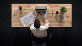 Den unga mannen arbetar på bärbara datorn, klockaplan av byggnad, i dag, arbetsbegreppet, kontorsbegreppet, kommunikation stock video