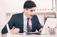 Den unga mannen arbetar på en dator Arkivbilder