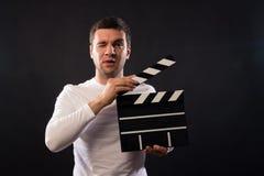 Den unga mannen av det Caucasian utseendet rymmer en clapperboard Por arkivfoto