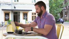 Den unga mannen avslutar maskinskrivning på bärbara datorn och kopplar av i kafé arkivfilmer