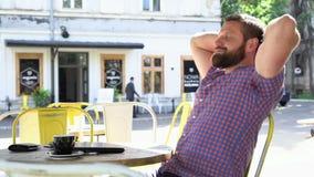 Den unga mannen avslutar maskinskrivning på bärbara datorn och kopplar av i kafét, glidareskotträtt stock video