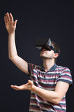 Den unga mannen bär exponeringsglas för virtuell verklighet 3D Isolerat på svart Royaltyfria Foton