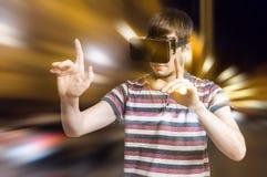 Den unga mannen bär hörlurar med mikrofon för virtuell verklighet 3D och spelar videospel Arkivbild