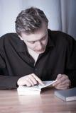 Den unga mannen böjde över boken arkivbilder