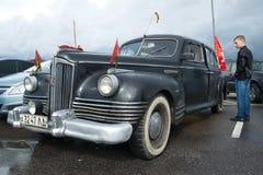 Den unga mannen betraktar den gamla sovjetiska bilen för regeringen ZIS-110 på en utställning av ett retro av bilar Arkivfoton