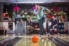 Den unga mannen bowlar med hans vänner som ser koncentrerade royaltyfri foto