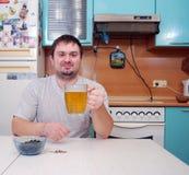 Den unga mannen dricker öl i kök Royaltyfria Bilder
