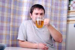 Den unga mannen dricker öl i kök Arkivfoton