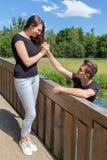 Den unga mannen erbjuder den röda rosen till den attraktiva flickvännen på bron in Royaltyfri Fotografi