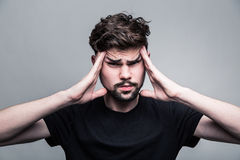 Den unga mannen erfar intensiv huvudvärk arkivbild