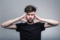 Den unga mannen erfar intensiv huvudvärk arkivfoton