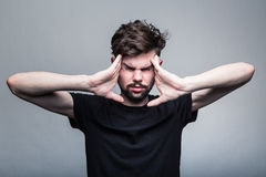 Den unga mannen erfar intensiv huvudvärk royaltyfri bild