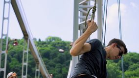 Den unga mannen fäster ett rep till en karbin för att hoppa från bron arkivfilmer