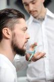 Den unga mannen får hans skägg för att klippa arkivfoton