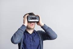 Den unga mannen förvånas av vad han ser i virtuell verklighetexponeringsglasen Fotografering för Bildbyråer