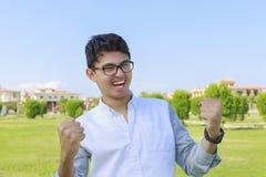 Den unga mannen firar hans seger som är lyckad Royaltyfri Bild