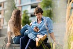Den unga mannen fokuseras på att använda smartphonen Arkivfoto