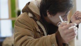 Den unga mannen från gatan dricker coctailen och ler i kafé 4K stock video