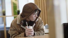 Den unga mannen från gatan dricker coctailen och värme händer i kafé 4K stock video
