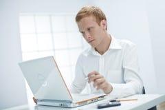 Den unga mannen fungerar på datoren. Arkivfoton