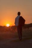 Den unga mannen går i solnedgång 1 Arkivbilder