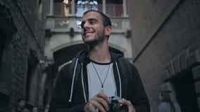 Den unga mannen går med kameran i gammal stad lager videofilmer