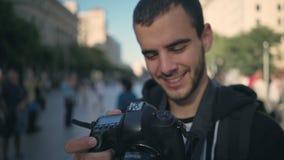 Den unga mannen går med kameran i gammal stad arkivfilmer