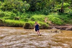 Den unga mannen går till och med en flod på vinandelinje i Chiang Mai i thailändskt royaltyfri foto