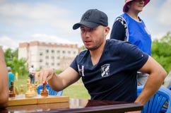 Den unga mannen gör en flyttning som spelar schack i amatörmässiga konkurrenser royaltyfria foton