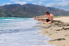 Den unga mannen gör en spark i ett hopp på stranden fotografering för bildbyråer