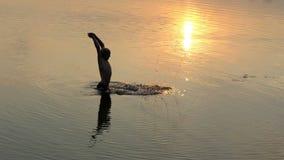 Den unga mannen gör färgstänk i en sjö på en solnedgång stock video