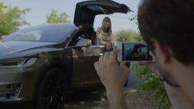 Den unga mannen gör fotoet av hans flicka nära den lyxiga bilen stock video