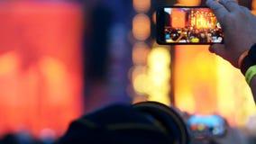 Den unga mannen gör fotoet genom att använda smartphonen som utomhus står på musikkonserten lager videofilmer