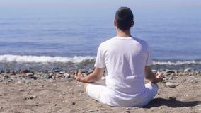 Den unga mannen gör meditation i lotusblomma att posera på havet/havstranden, harmoni och begrundande arkivfilmer