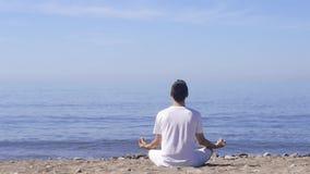 Den unga mannen gör meditation i lotusblomma att posera på havet/havstranden, harmoni och begrundande stock video