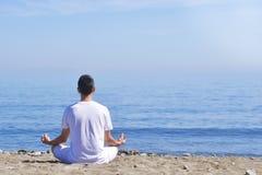 Den unga mannen gör meditation i lotusblomma att posera på havet/havstranden, harmoni och begrundande Praktiserande yoga för pojk Royaltyfria Foton