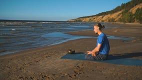 Den unga mannen gör meditation i lotusblomma att posera på havshavstranden, harmoni och begrundande arkivfilmer