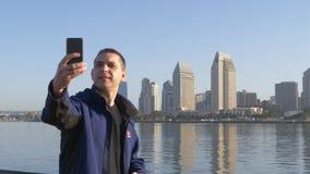 Den unga mannen gör selfie på bakgrund av centret stock video